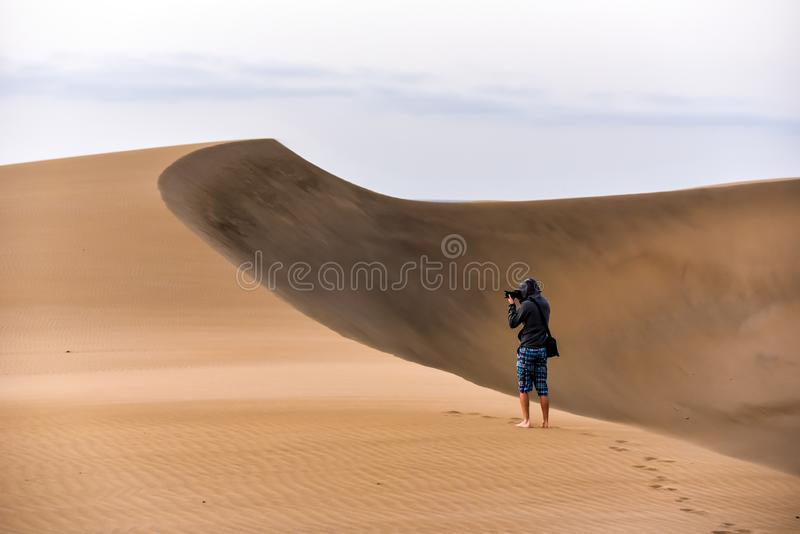 Photographer walking in the desert of gran canaria, spain royalty free stock photo