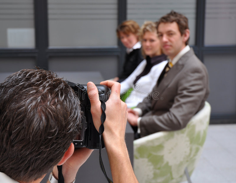 Photographer at work. Photographer shooting busienss youngsters at reception royalty free stock photos