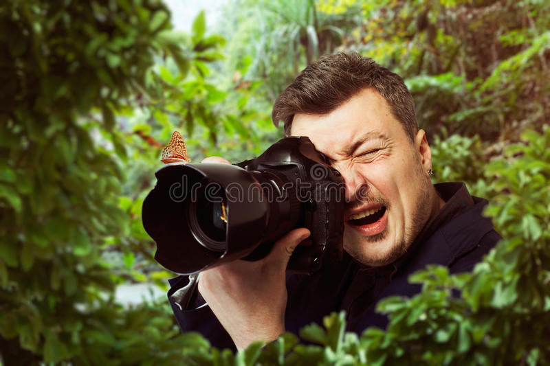 Photographer at work, butterfly on camera lens stock image
