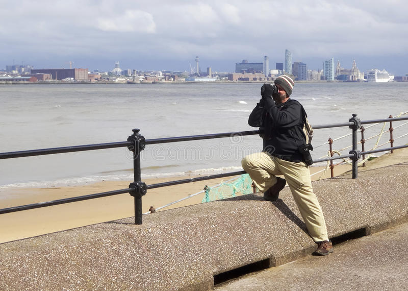 A Photographer Works Along Magazines Promenade, New Brighton. A Photographer Works Along Magazines Promenade in New Brighton, England royalty free stock images