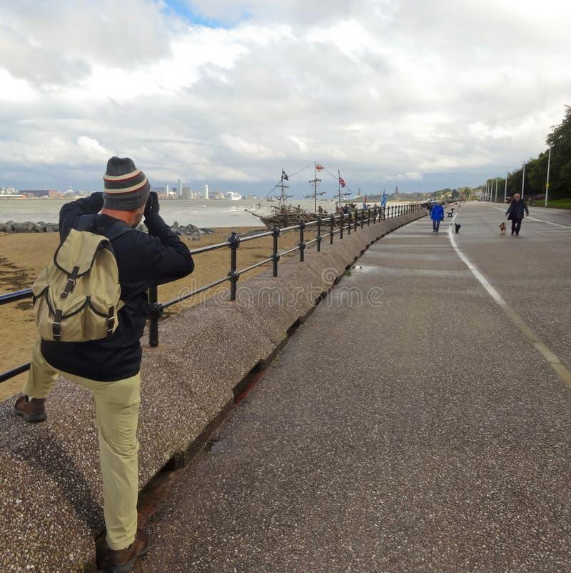 A Photographer Works Along Magazines Promenade, New Brighton. NEW BRIGHTON, ENGLAND, JUNE 29. Magazines Promenade on June 29, 2016, in New Brighton, England. A stock photo