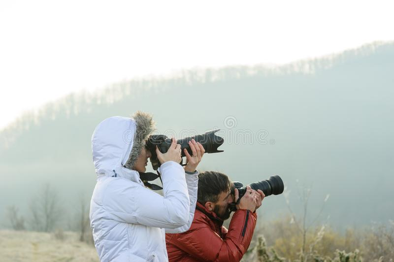 Photographers with cameras outdoor making landscape pictures. Photography, nature, professional, travel, man, background, mountain, male, sky, equipment royalty free stock images