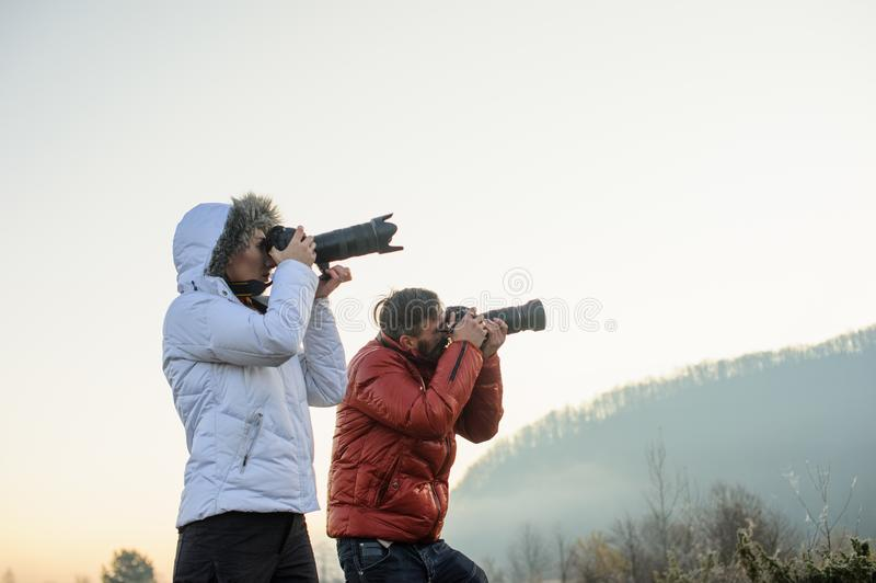 Photographers with cameras outdoor making landscape pictures. Photography, nature, professional, travel, man, background, mountain, male, sky, equipment stock photography