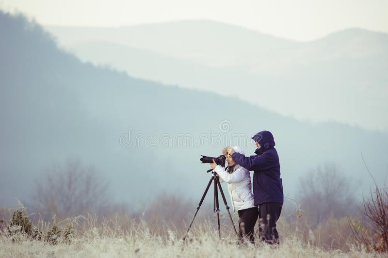 Photographers with cameras outdoor making landscape pictures. Photography, nature, professional, travel, man, background, mountain, male, sky, equipment royalty free stock photos