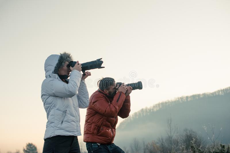 Photographers with cameras outdoor making landscape pictures. Photography, nature, professional, travel, man, background, mountain, male, sky, equipment stock photo