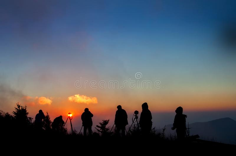 Photographers silhouetted against misty sunset in North Carolina mountains. Photographers silhouetted against misty sunset on top of Mt. Mitchell in Appalachian royalty free stock photos