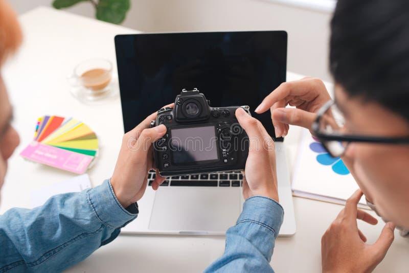 Photographes éditeur regardant l'appareil-photo dans le studio se reposant sur le bureau images stock