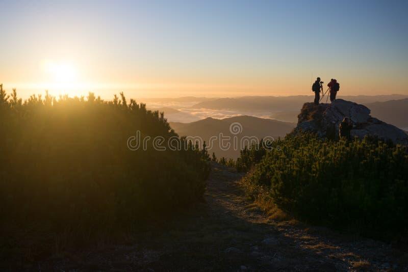 Photographes au lever de soleil dans les montagnes images stock
