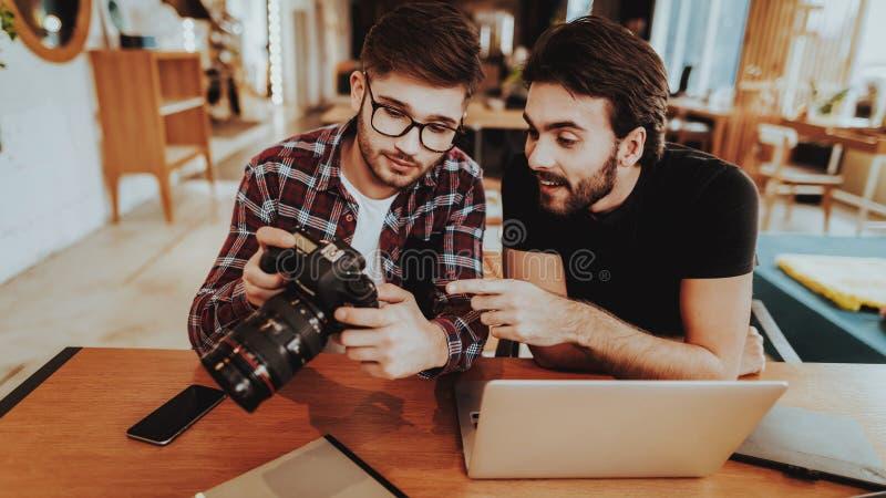 Photographes avec des travaux de caméra sur l'ordinateur portable à l'intérieur images libres de droits