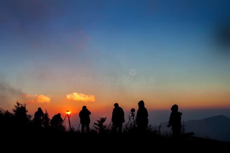 Photographes silhouettés contre le coucher du soleil brumeux en montagnes de la Caroline du Nord photos libres de droits