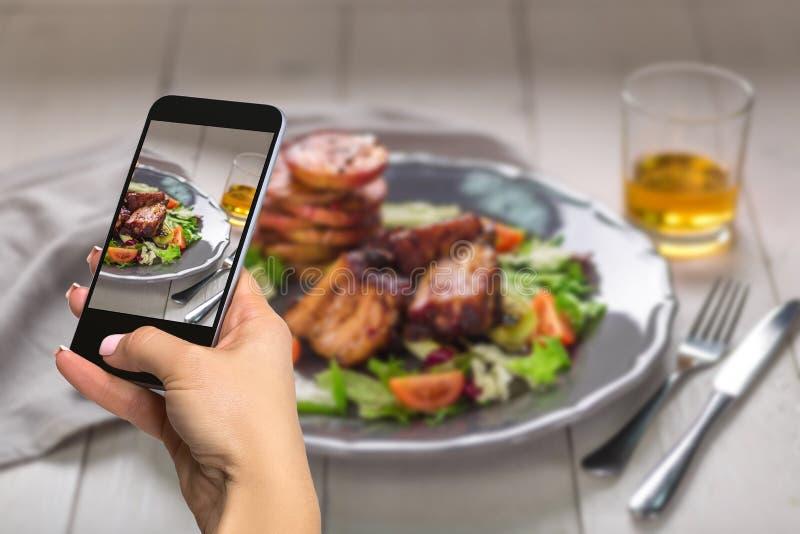 Photographiant le concept de nourriture - la femme prend la photo des plats chauds de viande Les nervures de porc ont grillé avec photos stock