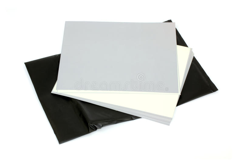 Photographic paper. Several sheets of old black and white photographic paper being exposed to light with the gray sheets already exposed and the white sheet stock photo