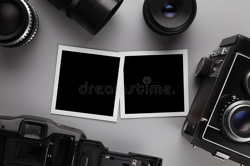 Photographic template - paper photo frames with blank space, lens and camera on gray table stock photo