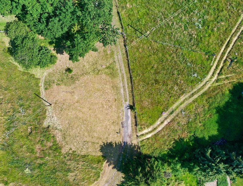 Photographie aérienne verticale d'une prairie sèche non entretenue sur un chemin de terre, où les voies mènent à la route photos libres de droits