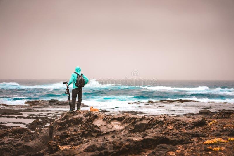 Photographie avec un chien recherchant le motif Vagues frappant le littoral rocheux volcanique La poussière du Sahara dans le cie images stock