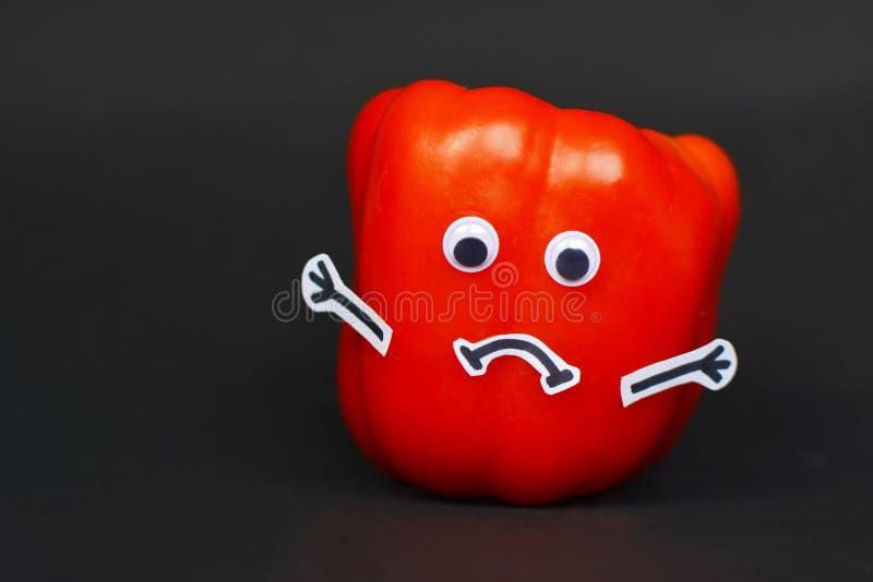 Photographie créative de nourriture de paprika mûr rouge avec les yeux drôles de lunettes, les mains de bâton et la bouche triste images libres de droits