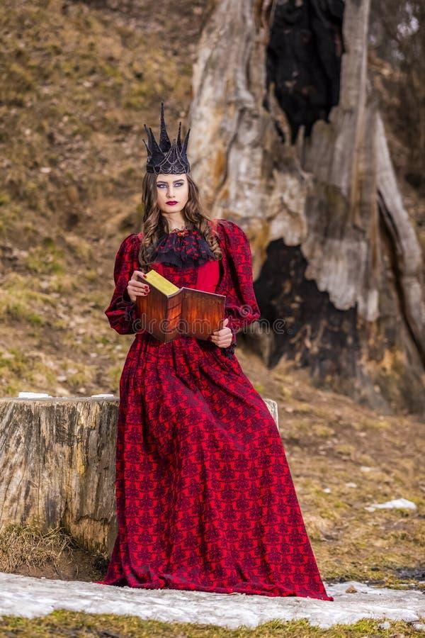 Photographie d'art Reine médiévale féerique mystérieuse dans la robe rouge et la couronne noire en épi posant avec le livre antiq photos libres de droits