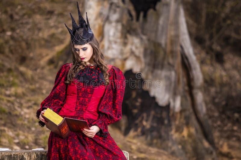 Photographie d'art Reine médiévale féerique mystérieuse dans la robe rouge et la couronne noire en épi posant avec le livre antiq photos stock
