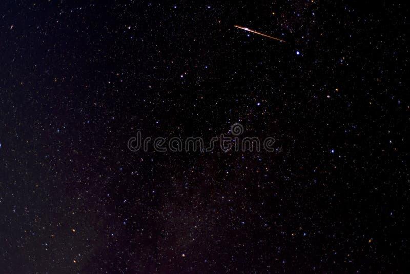 Photographie d'une étoile filante ou satellite qui passe au-dessus du ciel profond photographie stock libre de droits