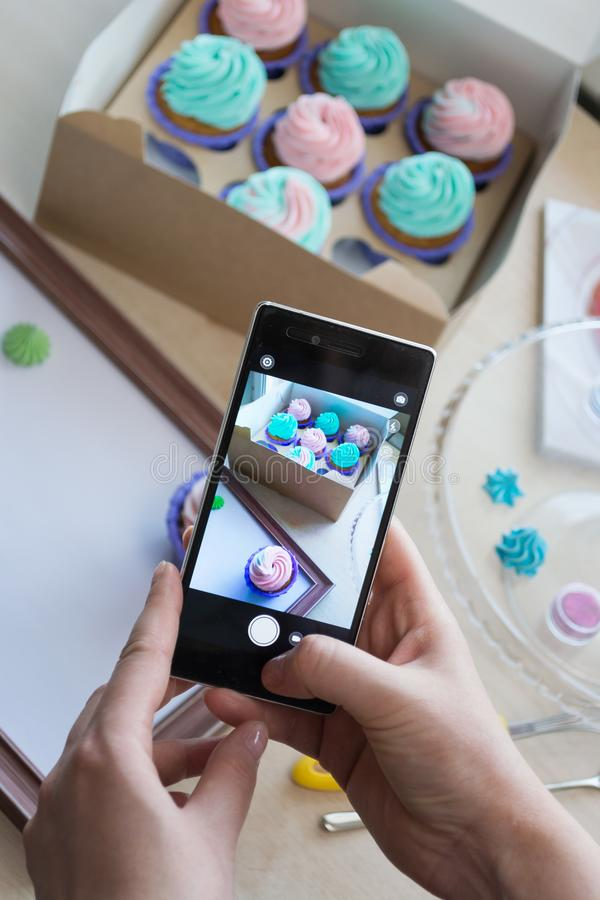 Photographie d'une boîte avec des petits gâteaux et d'un cadre en bois avec un téléphone photo libre de droits