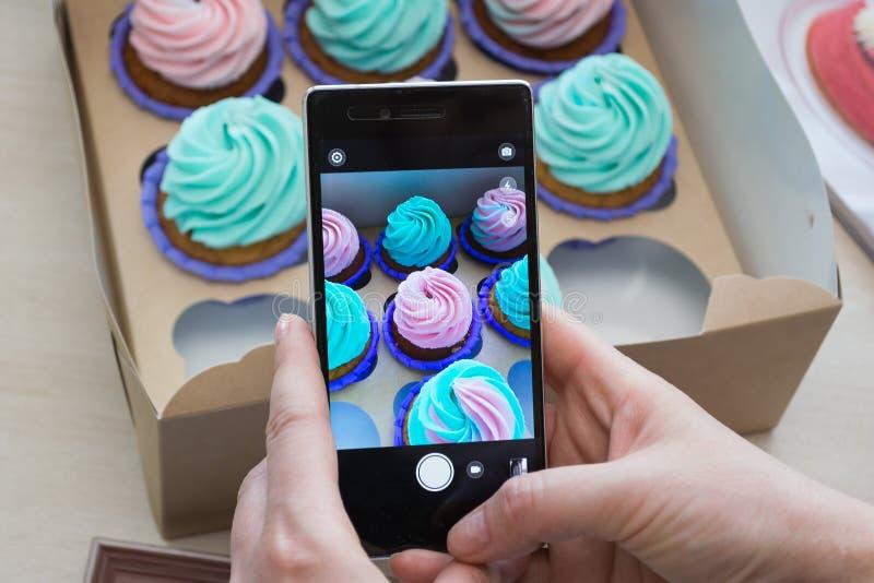 Photographie d'une boîte avec des petits gâteaux et d'un cadre en bois avec un téléphone image libre de droits