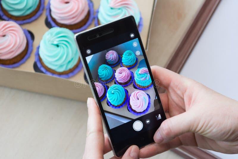 Photographie d'une boîte avec des petits gâteaux et d'un cadre en bois avec un téléphone photos libres de droits
