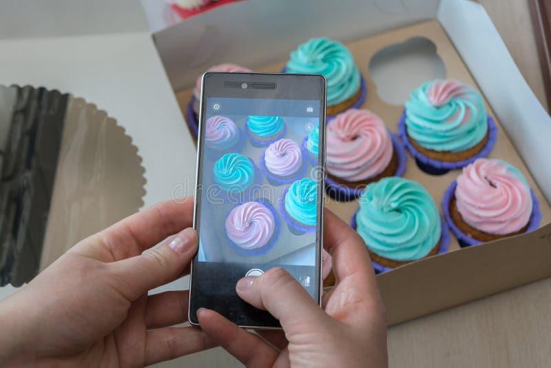 Photographie d'une boîte avec des petits gâteaux avec un téléphone photographie stock