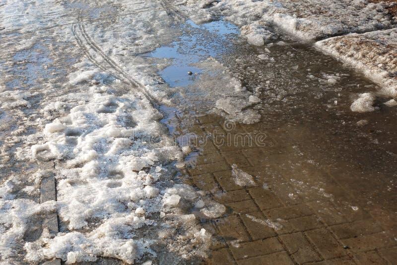 Photographie de plan rapproché de neige de fonte sur un trottoir fait de tuiles en béton grises photographie stock