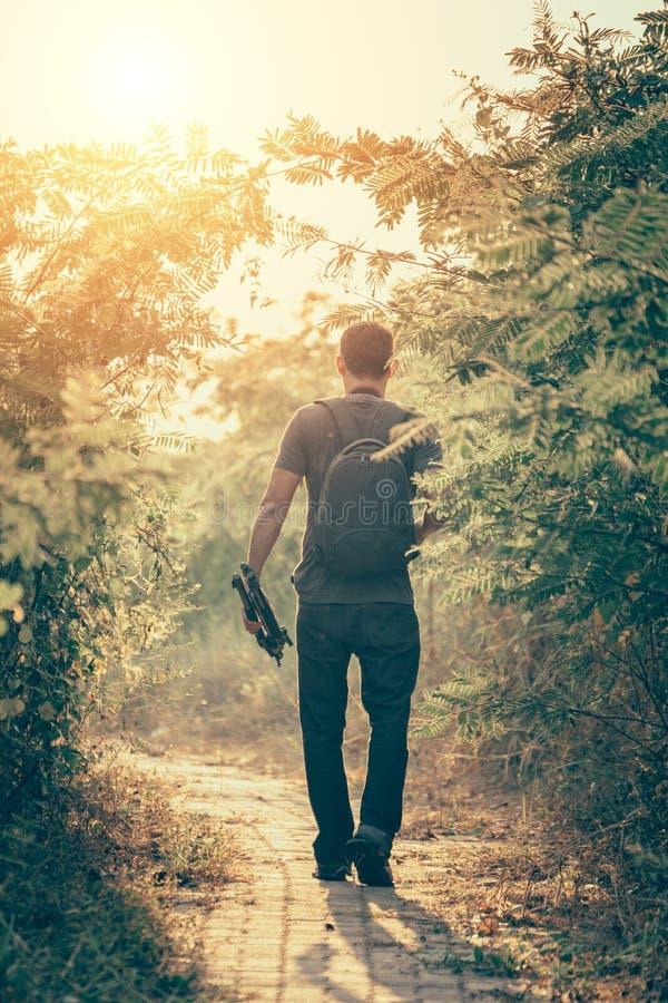 Photographie marchant sur le chemin dans la for?t avec le coucher du soleil l?ger, lever de soleil photographie stock libre de droits