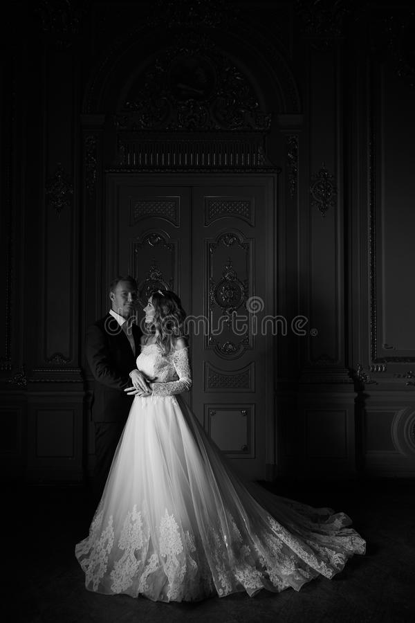 Photographie noire et blanche Couples de luxe de mariage dans l'amour Belle jeune mariée dans la robe blanche avec le bouquet de  photo stock
