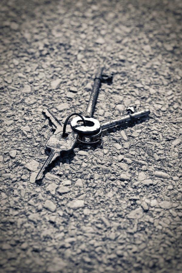 Photographie noire et blanche de vieilles clés rouillées se trouvant sur une voie concrète image libre de droits