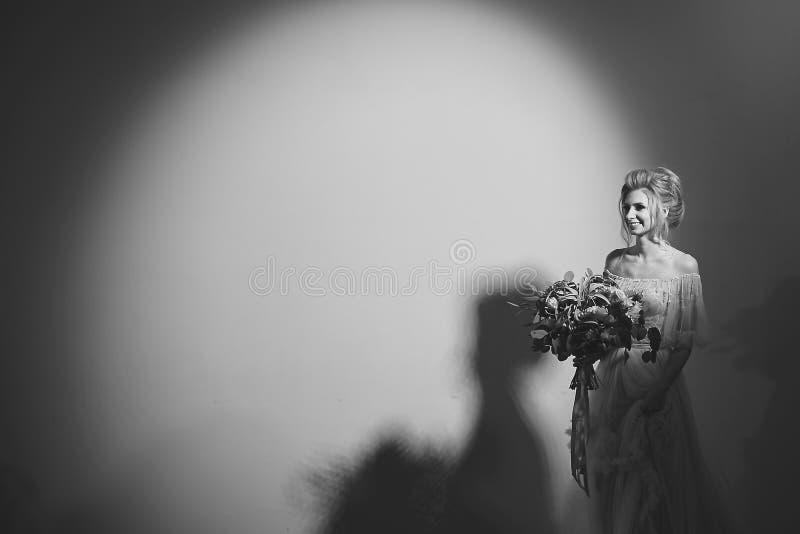 Photographie noire et blanche sans couleur d'art, une belle femme modèle dans une robe l'épousant élégante avec un bouquet des fl image stock