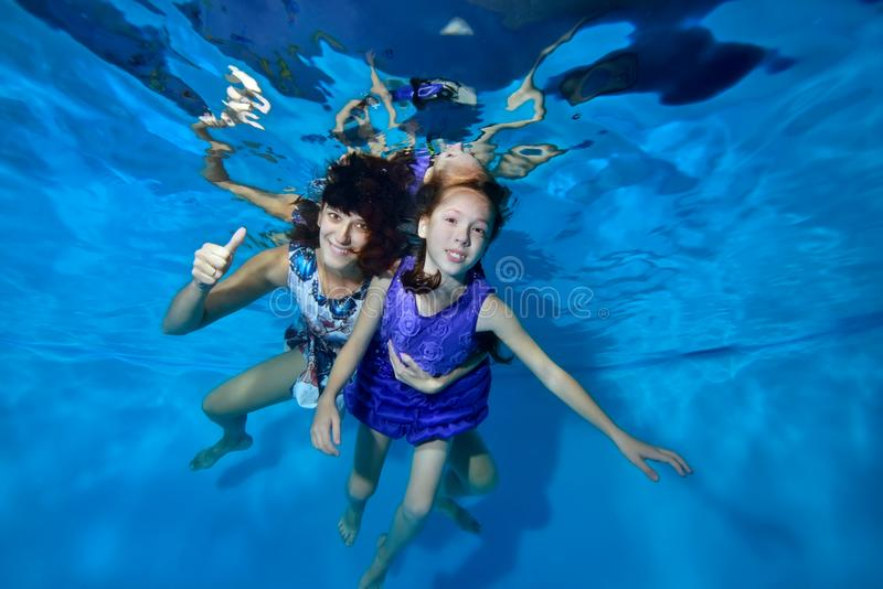 Photographie sous-marine La maman et la fille heureuses sont nageantes et jouantes sous l'eau dans la piscine dans de belles robe photos stock