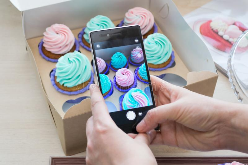 Photographing a box with cupcakes with a phone. By women`s hands, flatlay royalty free stock photography
