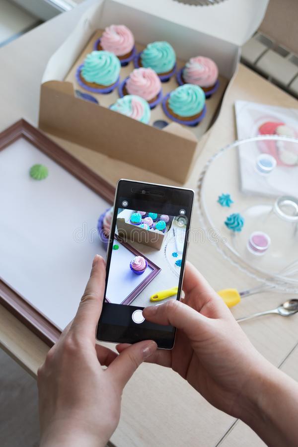 Photographing a box with cupcakes and a wooden frame with a phone. By women`s hands, flatlay stock image