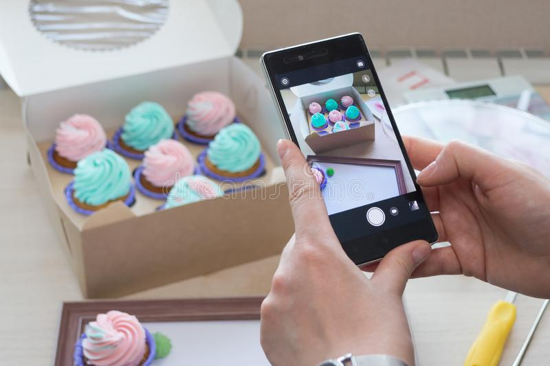 Photographing a box with cupcakes and a wooden frame with a phone. By women`s hands, flatlay royalty free stock photo