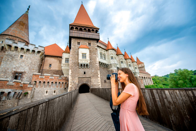 Photographing Corvin castle. Female tourist photographing with professional photo camera Corvin castle. Tourism in Romania, European country royalty free stock images
