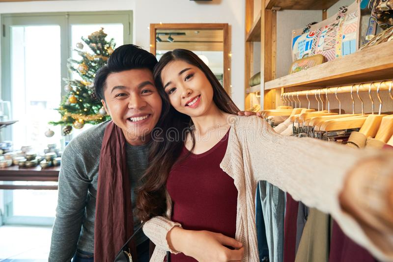 Photographing couple. Happy Asian couple photographing in the shop royalty free stock image
