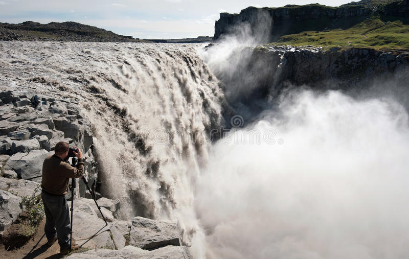 Photographing Dettifoss. Photographer taking picture of largest waterfall in Europe - Dettifoss from close distance, Iceland royalty free stock photo