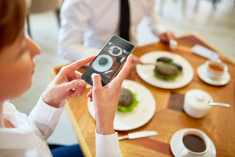 Photographing food. Businesswoman photographing sandwiches on plates while dining in cafe stock photography