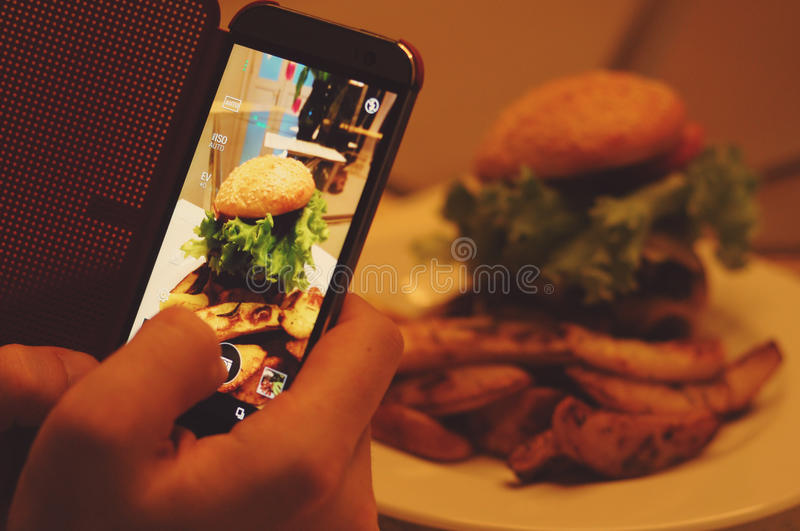 Photographing food at restaurant. Customer photographing food at restaurant for social media- closeup on hamburger royalty free stock images