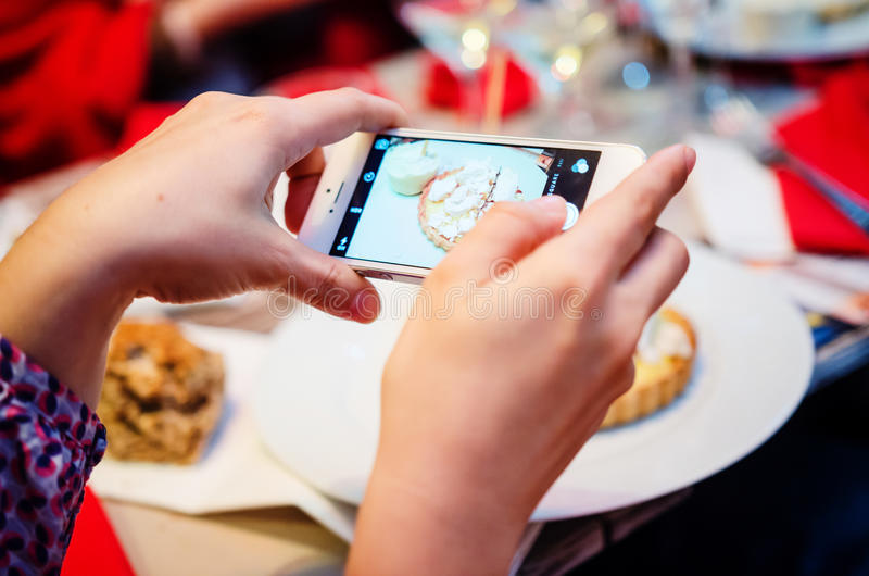 Photographing food at restaurant. Customers photographing food at restaurant for social media (lemon tart royalty free stock photo