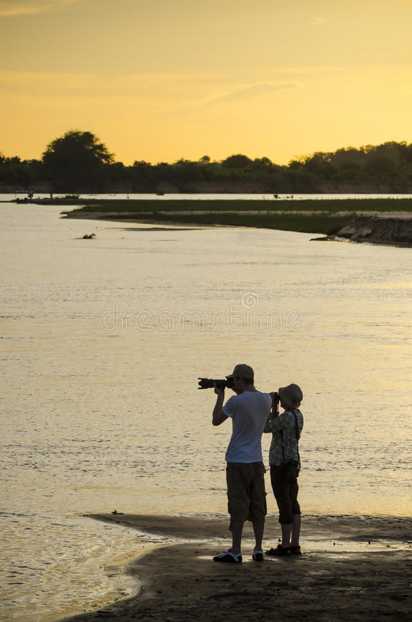 Photographing Rufiji river in sunset. Two persons photographing Rufiji river in sunset. Selous Game Reserve, Tanzania, Africa. The Selous was designated a UNESCO royalty free stock photos