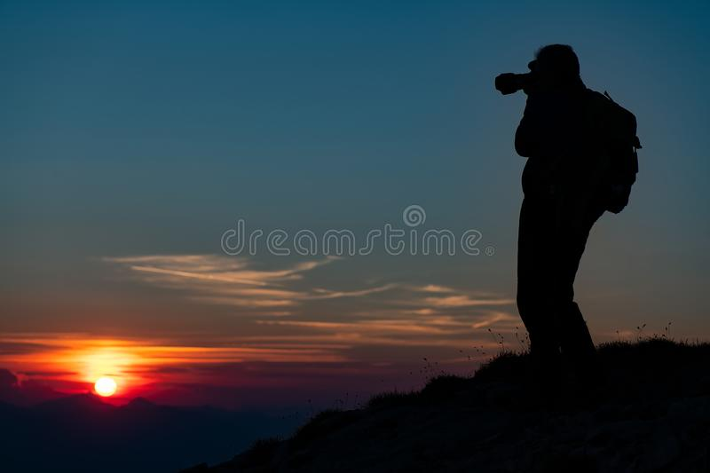 Photographing the sunset in the mountains. Photographer in silhouette royalty free stock images