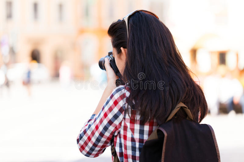 Photographing. Young beautiful tourist girl photographing in the city royalty free stock image