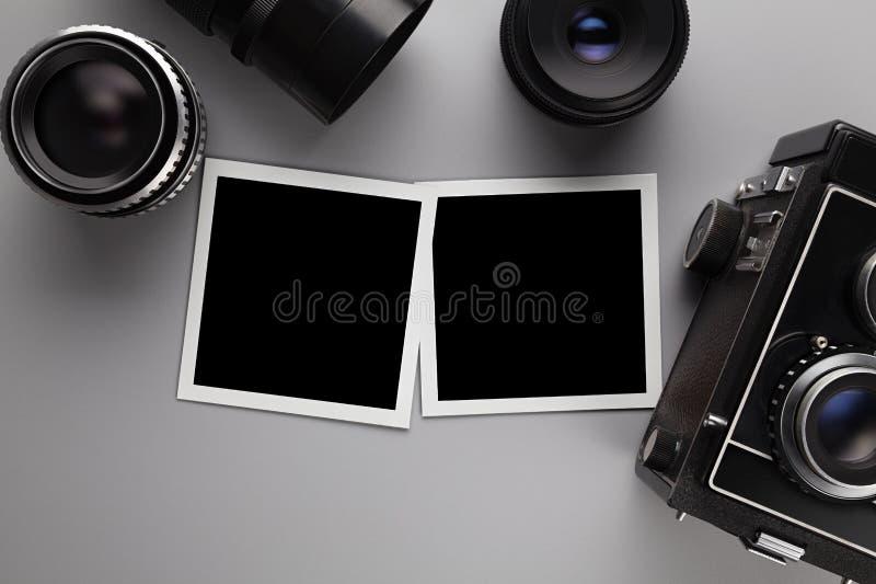 Photographische Schablone - Papierfotorahmen mit Leerstelle, Linse und Kamera auf grauer Tabelle lizenzfreies stockbild