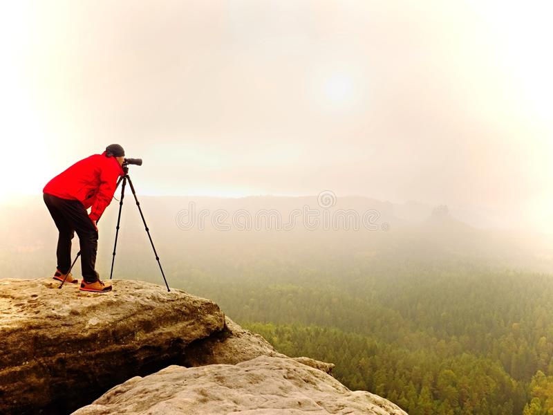 Photographr looking into viewfinder of dslr digital camera stand on tripod. Artist photographing mountain and cloudy landscape stock image