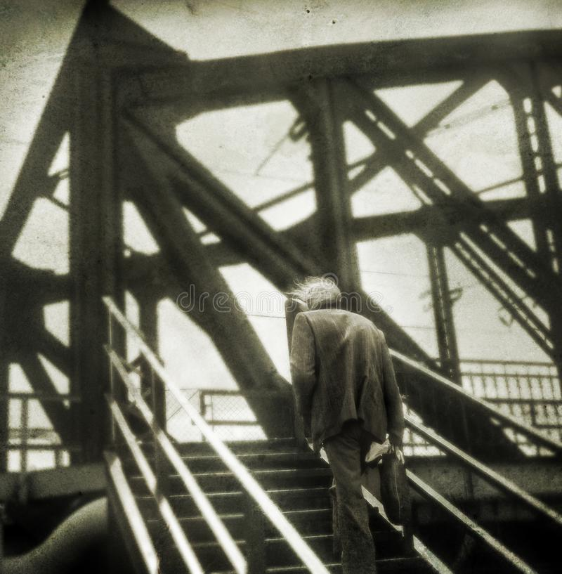 Photography film shot. Creative anonymous lonely man. Photography film shot. Lonely man at iron bridge. Visible grain and added textures to give pictorial stock photo