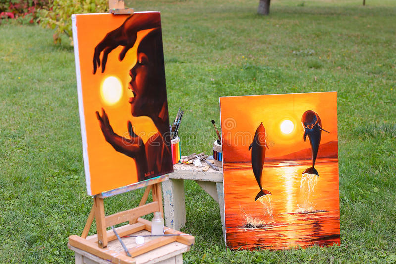 Photography and fine art paintings, which on easel in background. Photography and fine art paintings executed in warm shades of orange. One painting shows girl stock image