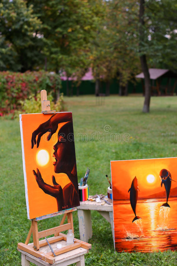 Photography and fine art paintings, which on easel in background. Photography and fine art paintings executed in warm shades of orange. One painting shows girl royalty free stock photography